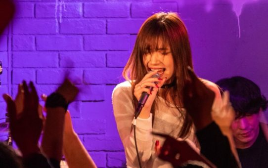 Rei singing at a one-man live
